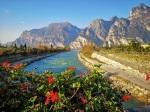 Pelargonie na tle rzeki i gór wokół Jeziora Garda