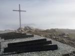 Krzyż i kierunkowskazy na szczycie Monte Stivo, na pierwszym planie kierunkowskaz na Jezioro Garda