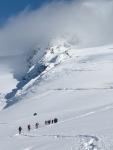 Grupa turystów podchodzi po śniegu na szczyt w Alpach