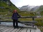Kobieta na drewnianym moście nad potokiem, na tle gór. Za nią szczyty Wysokich Taurów w Austrii