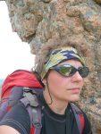 Kobieta w stroju sportowym na tle skały, na końcu szlaku GR 20 na Korsyce